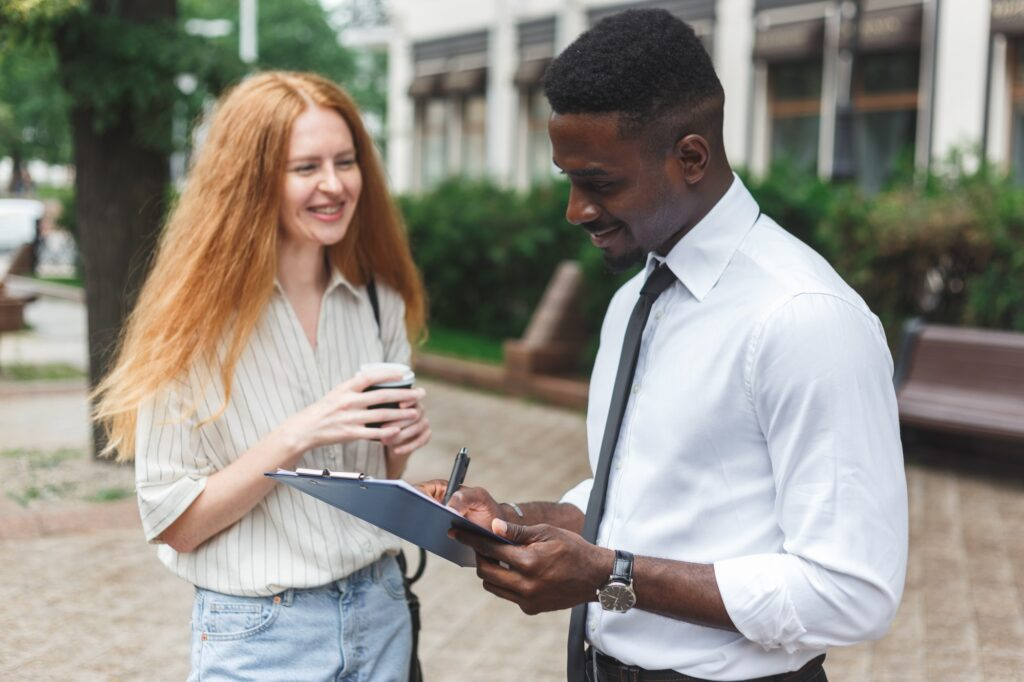Black african american man on the street making a survey to redhaired woman
